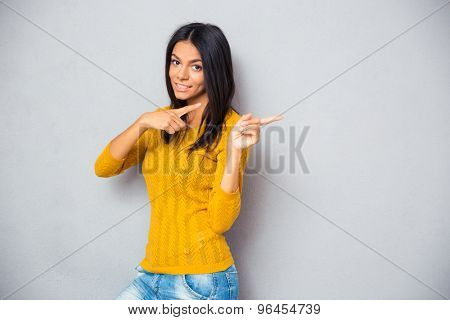 Happy woman showing finger away over gray background. Looking at camera