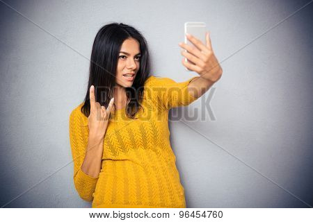 Happy young woman making selfie photo and showing victory sign over gray background