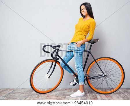 Full length portrait of a happy casual woman standing with bicycle on gray background. Looking at camera