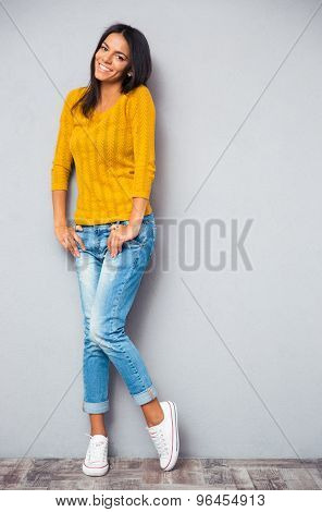 Full length portrait of a cute smiling woman posing on gray background. Looking at camera