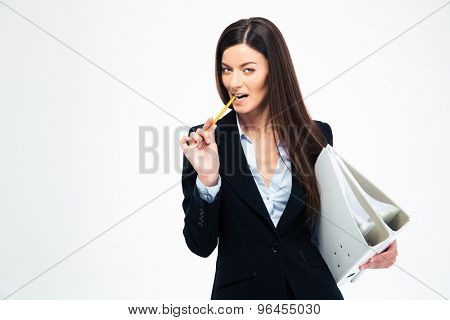 Businesswoman holding folders and biting pencil isolated on a white background. Looking at camera