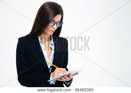 Businesswoman in glasses writing notes in notebook isolated on a white background