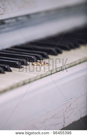 Wedding Gold Rings On The White Keys Of The Piano.