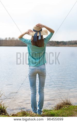 Girl In Hat Standing With Back Before Lake