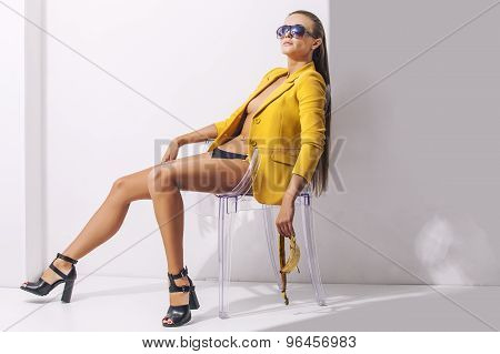 Full-length Portrait Young Elegant Woman In The Yellow Jacket, Shorts And Shoes With Heels On A Tran