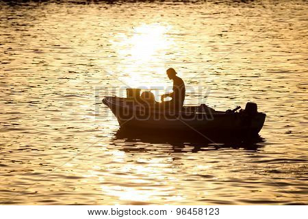 Man In Motor Boat At Sunset