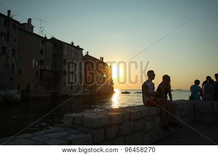 People Sitting On Coast At Sunset