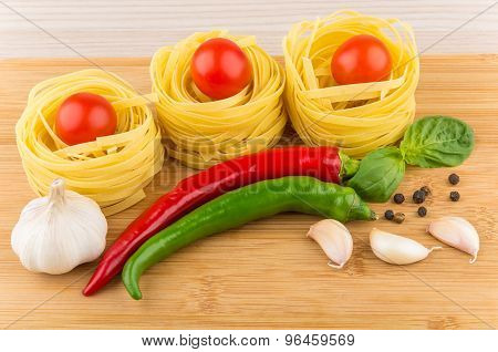Tagliatelle With Tomatoes, Garlic, Chili Peppers And Basil On Board