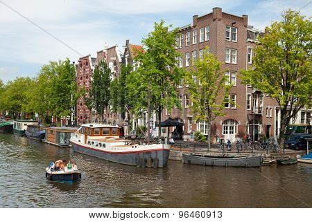 Group Of People Passing The Amsterdam Canals On A Boat