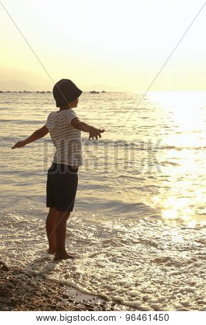 morning on the sea child arms outstretched basking in the sun