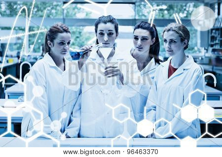 Science graphic against science students pouring liquid in a flask