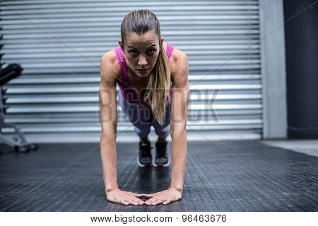 Portrait of a woman doing press up exercises at the crossfit gym