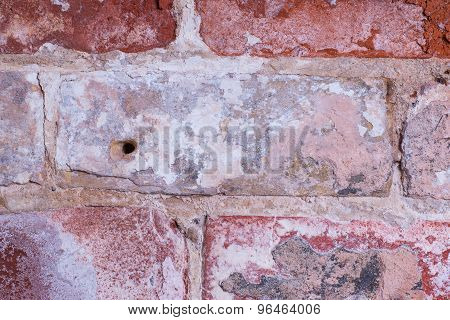 aged interior brick wall with worn and damaged brickwork