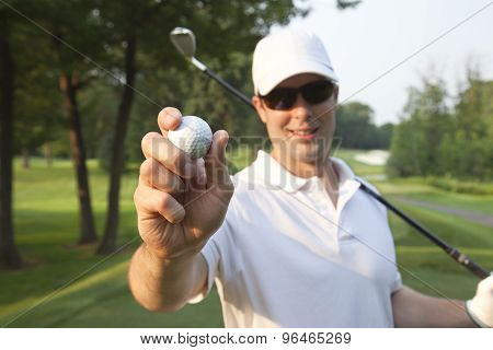 Selective Focus Of A Young Male Golfer Holding Golf Ball Out In Front