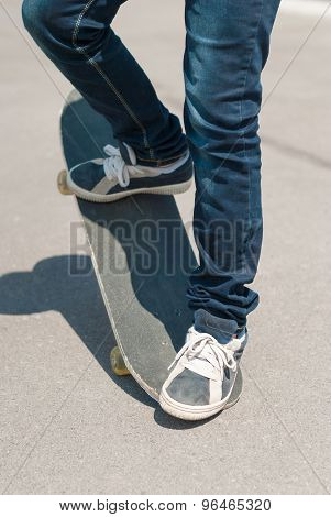 Skateboarder Jumping On A Skateboard On Asphalt.