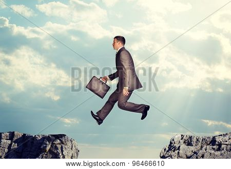 Businessman jumping over precipice
