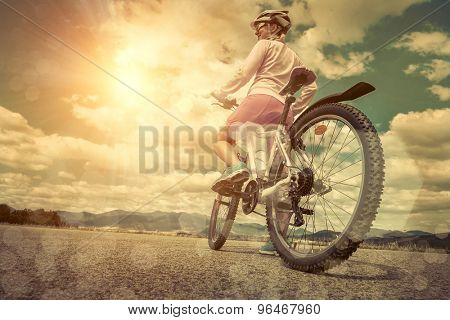Beautiful woman in helmet and glasses stay on the bicycle under sky with clouds.