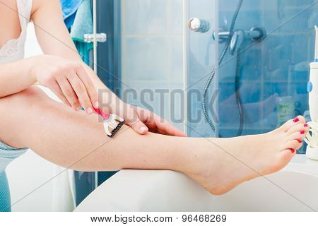 Woman Shaving Legs With Razor In Bathroom