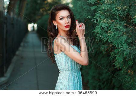 Beautiful Girl In A Dress With Earrings Near The Green Bush.