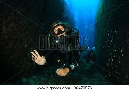 Female Scuba Diver exploring underwater reef and caves