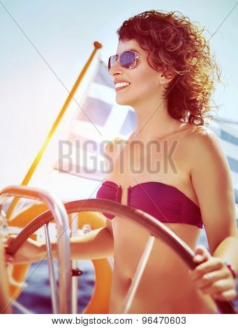 Joyful smiling woman driving sailboat, enjoying water travel along the Greek coast, active people lifestyle, enjoy the summer holidays