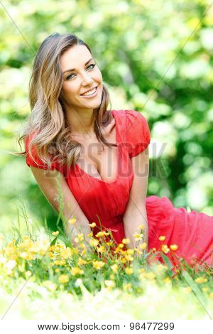 beautiful young woman in red dress sitting on grass