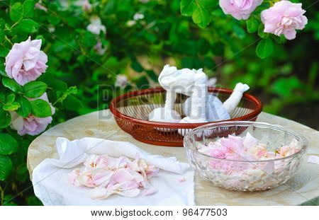 making herbal rose bags for spa and massage in front of rose garden