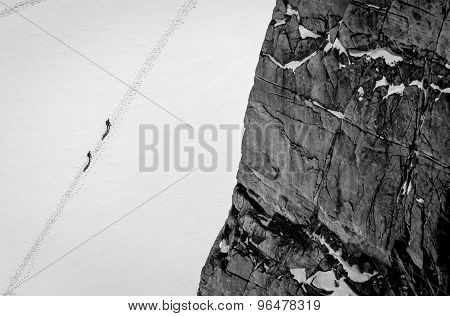 Mountaineers in snow with dramatic rocks