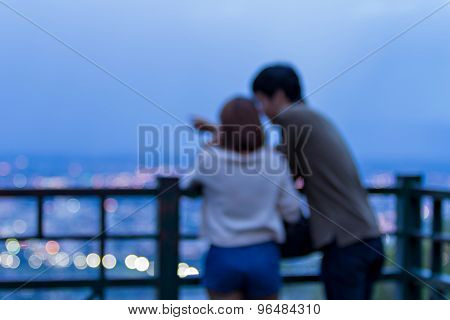 Defocused Young Couple Look To The City On Blue Time