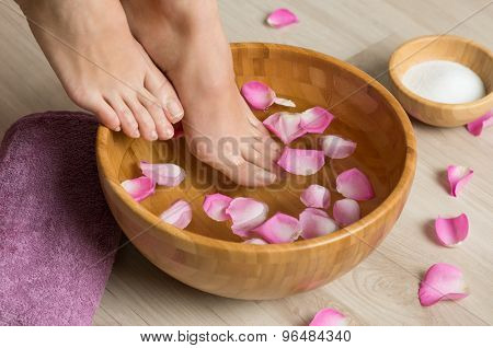 Closeup shot of a woman feet dipped in water with petals in a wooden bowl. Beautiful female feet at spa salon on pedicure procedure. Shallow depth of field with focus on feet.