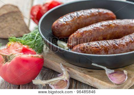 Fried Sausage, Tomato And Garlic Closeup.