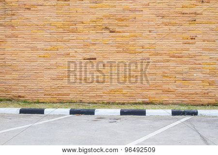 Empty Parking Lot With Brown Sandstone Wall