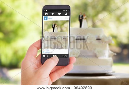 Female hand holding a smartphone against close-up of figurine couple on wedding cake