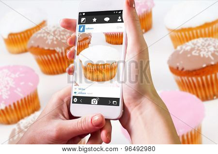 Hand holding smartphone against muffins with icing sugar