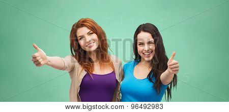 school, education, friendship, gesture and happy people concept - two smiling student girls or young women showing thumbs up over green chalk board background