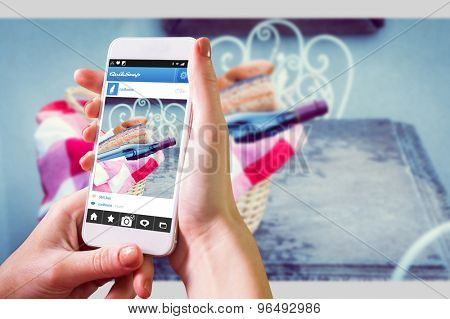 Hand holding smartphone against picnic basket of red wine and bread