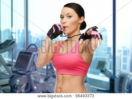 people, sport, fitness and healthy lifestyle concept - asian woman coach blowing whistle over gym machines background