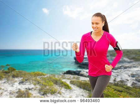 sport, fitness, health, technology and people concept - smiling young african american woman with smartphone and earphones running on beach and listening to music