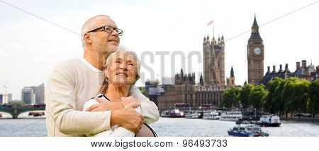 family, age, tourism, travel and people concept - happy senior couple over houses of parliament or palace of westminster and big ben clock tower in london