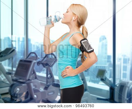 sport, fitness, technology and people concept - smiling sporty woman with smartphone and earphones listening to music and drinking water over gym machines background
