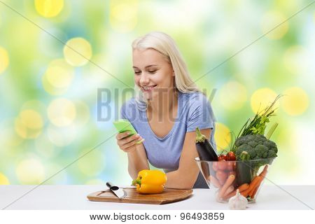 healthy eating, vegetarian food, dieting and people concept - smiling young woman with smartphone cooking vegetables over summer green holidays lights background
