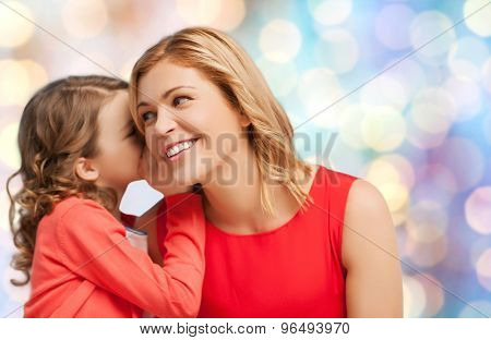 people, motherhood, family and adoption concept - happy mother and daughter whispering something into ear over blue holidays lights background