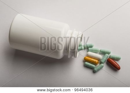 White pills and pill bottle on white background