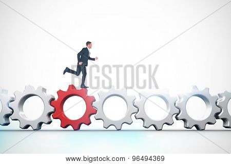 Businessman running against red and white cogs and wheels