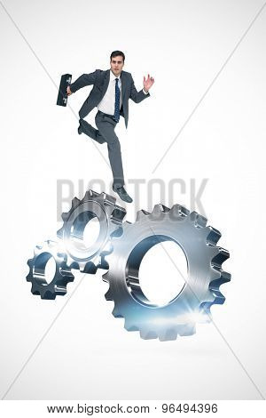 Stern businessman in a hurry against metal cog and wheel connecting