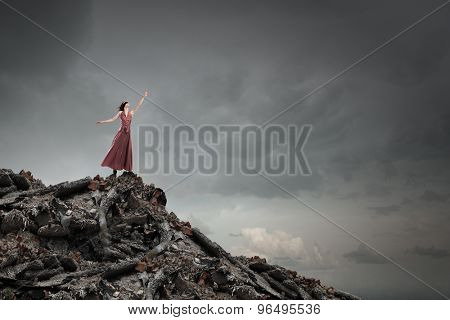 Young woman in evening dress and blindfold standing on mountain top