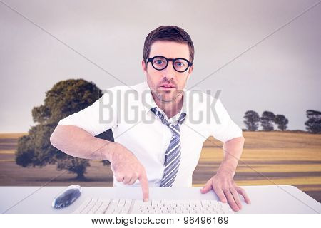 Businessman working at his desk against bright brown landscape