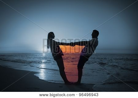 Couple holding hands on balcony against romantic couple at sunset