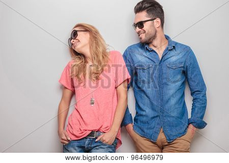 Happy young caouple laughing together while holding hands in pockets.