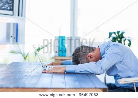 Businessman lying on his desk in office